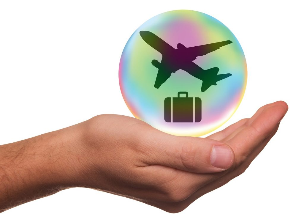 Hand with earth bubble and airplane and luggage
