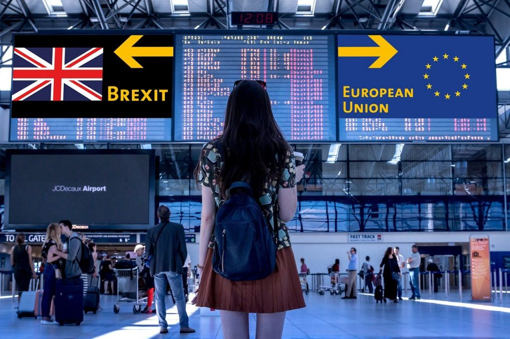 Woman in front of display at airport showing Brexit or European Union in different directions